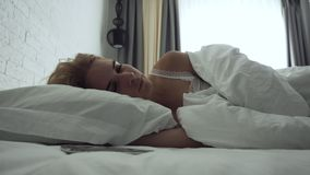 Sleepy woman turns alarm off while awakening in the morning. stock video footage