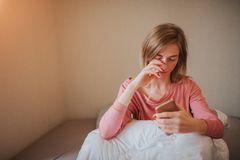 Sleepy young woman waking up with alarm. She overslept to work.  Royalty Free Stock Photography