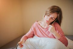 Sleepy young woman waking up with alarm. She overslept to work.  Royalty Free Stock Photo