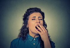 Sleepy young woman with wide open mouth yawning eyes closed Royalty Free Stock Photo