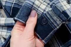 Sleeve of blue checkered shirt in female hand. Close-up. Sleeve of blue checkered shirt in female hand. Close-up Stock Photography