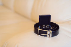 Sleeve Links and Belt. Sleeve links in box and leather belt on bed stock photos