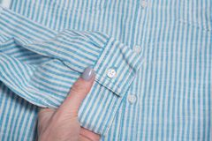 Sleeve of striped blue and white shirt in female hand. Close-up stock photos