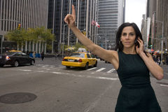 Sleeveless getting cab. Woman executive hails a cab while talking on a cell phone in a busy urban area stock photos