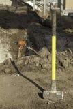 Sleg hammer on construction site. Yellow sleg hammer on construction site with a jack hammer in the background Royalty Free Stock Photos