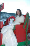 Sleigh Bride. Winter wonderland bride. Beautiful bride sitting in a red sleigh stock photo