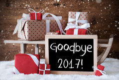 Sleigh With Gifts, Snow, Snowflakes, Text Goodbye 2017. Sled With Christmas And Winter Decoration And Snowflakes. Gifts And Presents On Snow With Wooden stock photography
