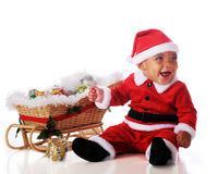 Sleigh-Ride Ready. An adorable biracial Santa happy sitting by a wicker sleigh filled with Christmas decorations.  Isolated on white Royalty Free Stock Photo