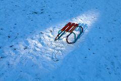 Sleigh in spot of sun light on blue snow field Royalty Free Stock Photography