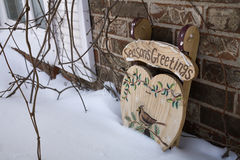 Sleigh. A tole painted Seasons Greetings and bird are seen on a miniature wooden sleigh in snow Stock Images