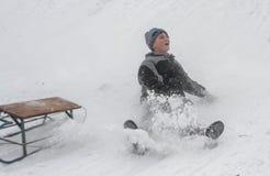 sleighing在小山的孩子 免版税库存图片