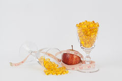 Slender apple with 2 glasses of fish oil Stock Image