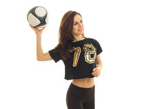 Slender athletic brunette looks away and raised in hand soccer ball Royalty Free Stock Photos