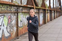 Slender athletic woman jogging on a bridge. Alonge old rusty metal girders and graffiti covered walls royalty free stock photos
