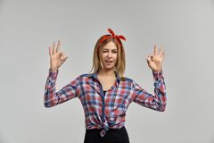 Slender attractive young blonde woman winks and shows OK sign. Studio portrait on isolated background Royalty Free Stock Photography