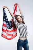 Slender auburn-haired woman lifting up US flag Royalty Free Stock Image