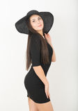 Slender beautiful Asian girl in little black dress and a black wide-brimmed hat Stock Images