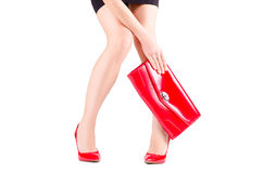 Slender beautiful female legs in red shoes and mini bag in hand. Isolated on white background Royalty Free Stock Photo