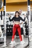Slender beautiful girl is doing back squats and strong athletic man insures her in the modern gym stock photos