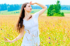 Slender beautiful girl in flower field Stock Photos