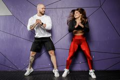 Slender beautiful girl in sports clothes and strong athletic man jump on the background of stylish violet wall stock photography