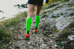 Slender and beautiful legs girls. Closeup slender and beautiful legs of girl running uphill on track in compression socks. fitness and exercise in mountains Royalty Free Stock Photography