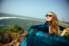 Slender beautiful woman girl on sea rock with pareo shawl royalty free stock photography