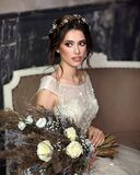Slender beautiful woman in a luxurious wedding dress. Portrait of the bride with a white bouquet in her hands