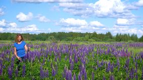 A slender beautiful woman, walks through the meadow among the purple flowers and smiles on a Sunny day. A slender beautiful woman walks through the meadow among stock video footage