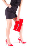 Slender beautiful womanish feet in red shoes and mini bag. Isolated Stock Photography