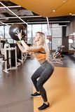 Slender blond girl with long hair dressed in a sportswear is doing back squats with heavy fitness ball in the modern royalty free stock photo