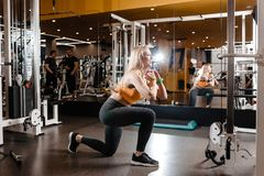 Slender blond girl with long hair dressed in a sportswear is doing back squats in the modern gym next to the mirror royalty free stock photos