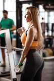 Slender blond girl with long hair dressed in a sportswear is doing exercises with dumbbells in the modern gym with big stock photos