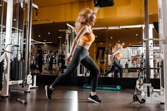 Slender blond girl with long hair dressed in a sportswear is jumping in the modern gym next to the mirror stock photo