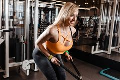 Slender blond girl with long hair has a TRX workout in the modern gym full of sun light royalty free stock photo