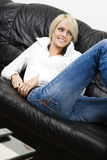Slender blond woman in jeans relaxing at home Stock Photography