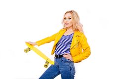 A slender blonde girl with a yellow skate in her hands on an isolated white background. stock image