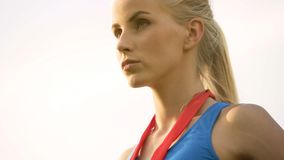 Slender blonde lady proudly looking forward, won medal in sports competition. Stock photo royalty free stock image