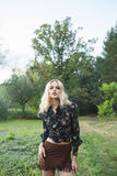 The slender blonde woman in a short brown skirt and a dark shirt in the forest. Hippie style Stock Photography