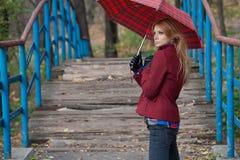 Slender blonde woman standing on the pedestrian bridge under the Royalty Free Stock Photo
