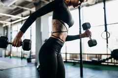 Slender body of a young woman with tattoo in a black sportswear that is doing exercises with dumbbells in the gym royalty free stock photography