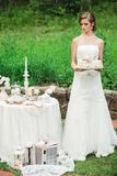 Slender bride with a cake in her hands stock photo