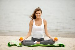 Slender brunet girl holds oranges in her hands siting in the lotus position on a yoga mat on sandy beach on a warm windy stock image