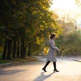 Slender brunette girl in beige coat crossing empty street at sun Stock Photo