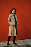 Slender brunette girl in beige coat with spectacles at maroon wa Royalty Free Stock Photos