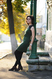 Slender brunette girl in green dress with spectacles by column a Stock Images