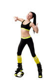 Slender brunette girl in kangoo jumps shoes showing a fingers up Stock Image