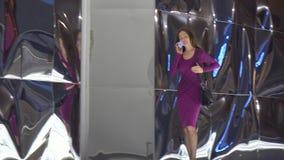 Slender brunette girl in purple dress walking and talking on her telephone. 4K pan shot stock video footage