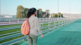 Slim sportive woman is walking to training on stadium, carrying backpack. Slender brunette girl is strolling over track in open stadium. She is going to doing stock video