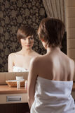 Slender brunette in towel posing near mirror Stock Photography